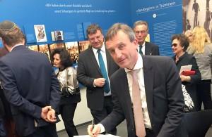 Düsseldorfs OB Thomas Geisel trägt sich ins Gästebuch ein.
